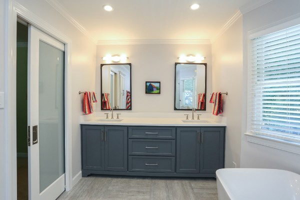 Beautiful modern bathroom with dark gray cabinets and bright LED lighting after remodel